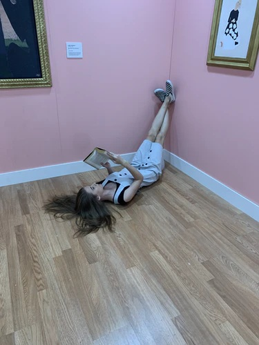 A Girl Reading A Book While Laying Down on the Floor with Her Legs Propped Up on the Wall