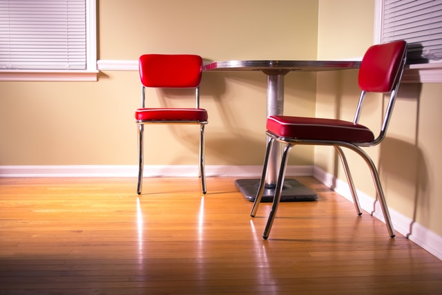 Two chairs and a table placed in the corner